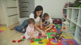 Mãe nova que joga com os tijolos com crianças filme