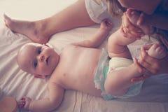 Mãe nova que joga com seu bebê na cama Fotografia de Stock