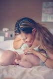 Mãe nova que joga com seu bebê na cama Imagem de Stock Royalty Free