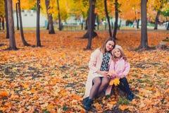 Mãe nova que joga com sua filha no parque do outono foto de stock