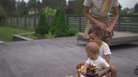 Mãe nova que joga e que tem o divertimento com seus irmãos do filho do bebê em um jardim verde com carros - valores familiares mo filme