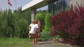 Mãe nova que joga e que tem o divertimento com seus irmãos do filho do bebê em um jardim verde - verão morno da cor dos valores f filme