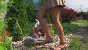 Mãe nova que joga e que tem o divertimento com seus irmãos do filho do bebê em um jardim verde - verão morno da cor dos valores f vídeos de arquivo