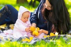 Mãe nova que mostra a seu bebê maçãs frescas do outono imagem de stock