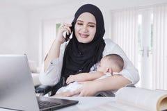 Mãe nova que nutre seu bebê ao trabalhar Fotografia de Stock