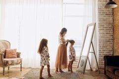 A mãe nova que penteia a posição do cabelo da sua filha pequena na frente do espelho e de sua segunda filha entra-lhes foto de stock