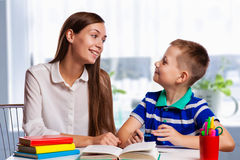 Mãe nova que senta-se em uma tabela em casa que ajuda seu filho pequeno com seus trabalhos de casa da escola como escreve notas e Imagens de Stock