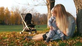 Mãe nova que senta-se na grama e que guarda seu bebê pequeno Parque sunlight video estoque