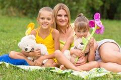 Mãe nova que senta-se no piquenique em um esclarecimento com duas filhas Fotos de Stock Royalty Free