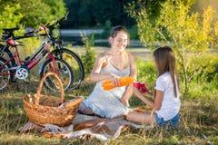 Mãe nova que tem o piquenique pelo rio com filha Mãe po Imagens de Stock Royalty Free