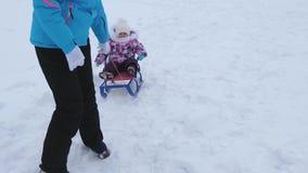 A mãe nova rola pouco bebê no trenó ao longo da estrada nevado no inverno A criança é impertinente e gritos ao sentar-se no trenó vídeos de arquivo