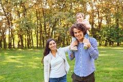 A mãe, o pai e a filha estão andando no parque fotografia de stock