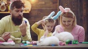 A mãe, o pai e o filho estão pintando ovos A família feliz está preparando-se para a Páscoa Coelho vestindo do menino bonito da c