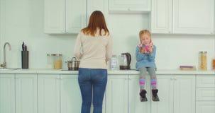 Mãe ocupada que faz tarefas de agregado familiar na cozinha filme