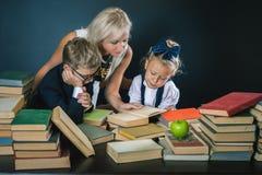 A mãe ou o professor que ajudam para a escola caçoam fazer os trabalhos de casa, lendo Imagem de Stock