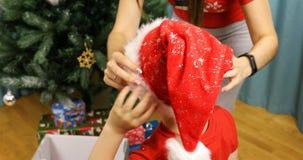 A mãe põe seu filho sobre a cabeça com um chapéu do ano novo para Santa Claus vídeos de arquivo
