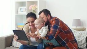 Mãe, pai e bebê com PC da tabuleta em casa filme
