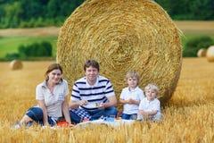 Mãe, pai e dois filhos pequenos tomando parte num piquenique junto Foto de Stock