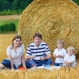 Mãe, pai e dois filhos pequenos tomando parte num piquenique junto Fotografia de Stock