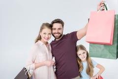 Mãe, pai e filha estando com sacos de compras fotografia de stock royalty free