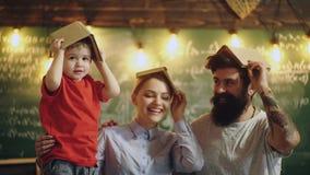 Mãe, pai e filho com os livros em suas cabeças Mantenha o conhecimento da informação na mente Cabeça como o armazenamento da info vídeos de arquivo
