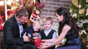 Mãe, pai e filhos olhando presentes do Natal, família que comemora o ano novo, sentando-se na sala de visitas em casa próximo filme