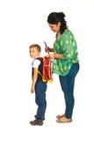 A mãe prepara o menino para a escola imagens de stock