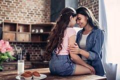 Mãe que abraça a filha que senta-se na tabela imagens de stock royalty free