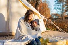 Mãe que abraça sua criança com uma cobertura ao sentar-se perto da barraca de acampamento foto de stock