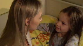 Mãe que abraça sua filha goodnight no quarto video estoque