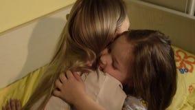 Mãe que abraça sua filha goodnight no quarto vídeos de arquivo