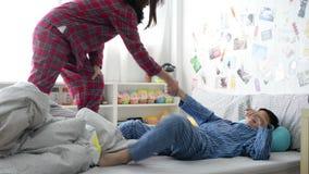 Mãe que acorda seu filho preguiçoso no quarto video estoque