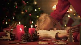 Mãe que afaga menina agradável adormecida caído perto belamente das decorações X-mas, casa video estoque