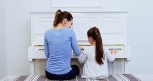 Mãe que ajuda à filha em jogar o piano 4k filme