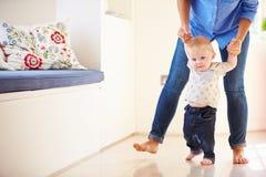 Mãe que ajuda o filho novo como aprende andar imagem de stock