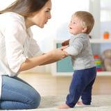 Mãe que ajuda seu filho a andar em casa imagens de stock