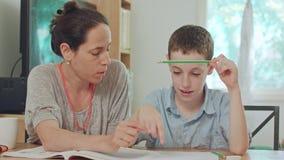 Mãe que ajuda seu filho a fazer em casa seus trabalhos de casa video estoque