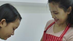 Mãe que ajuda sua filha no avental vestindo em uma casa confortável vídeos de arquivo