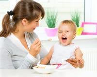 Mãe que alimenta seu bebê Fotos de Stock Royalty Free