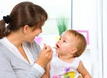 Mãe que alimenta seu bebê Fotos de Stock