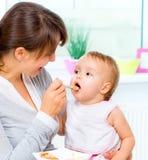 Mãe que alimenta seu bebê fotografia de stock royalty free