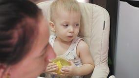 Mãe que alimenta seu filho do bebê com colher Sira de mãe a dar o alimento saudável a sua criança adorável em casa Bebê feliz com video estoque