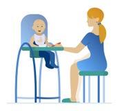Mãe que alimenta uma jovem criança no cadeirão Fotografia de Stock