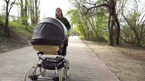 Mãe que anda com o transporte no parque video estoque