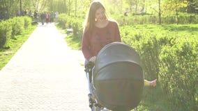 Mãe que anda com o transporte no parque vídeos de arquivo