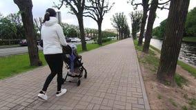 Mãe que anda com um carrinho de criança de bebê ao longo da terraplenagem da cidade vídeos de arquivo