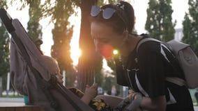 Mãe que anda com um carrinho de criança de bebê no parque da cidade filme