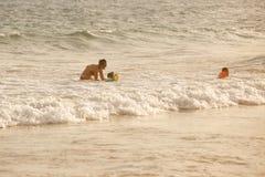 Mãe que aprecia as ondas do mar, nadando com suas crianças fotografia de stock