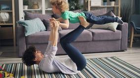 Mãe que aumenta seu filho com os pés que fazem a ioga no assoalho que tem o divertimento junto