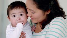 Mãe que beija seu bebê no mordente video estoque